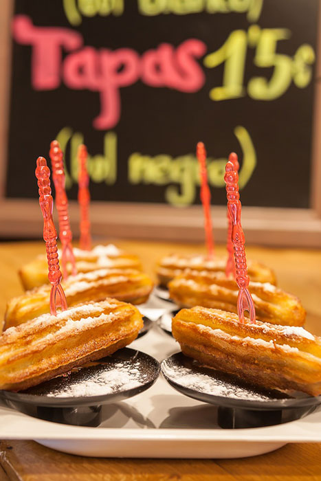 """PINTXO- Chocolate-filled """"churro"""" (finger doughnut) with syrup, icing sugar and chocolate flakes"""
